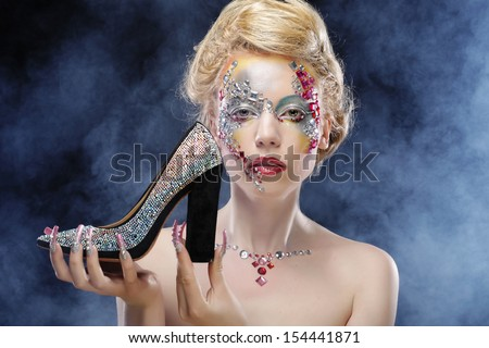 Closeup portrait of woman with artistic make-up holding shoe over smoke background