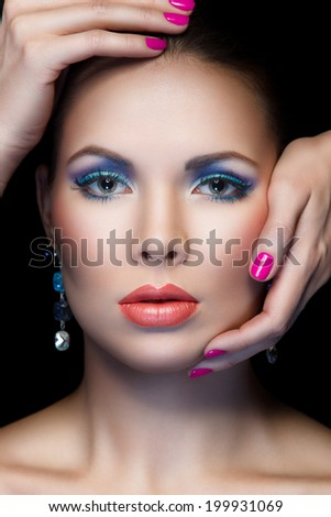 closeup portrait of woman with beautiful makeup and hands on her face on black background
