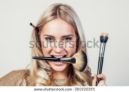Closeup portrait of woman with makeup brush near face - stock photo