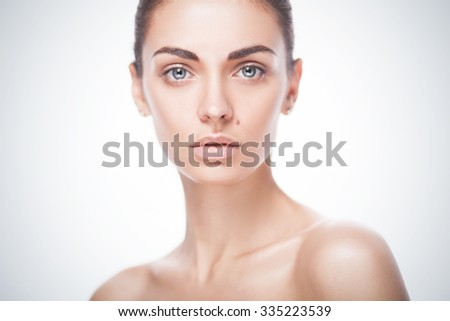 closeup portrait of young adult woman with clean fresh skin isolated on blue gradient background - stock photo