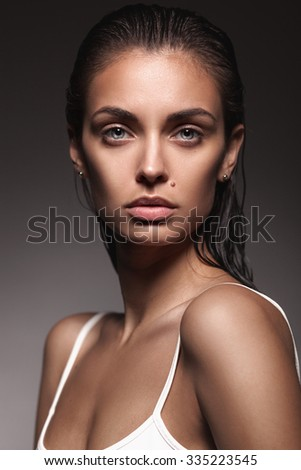 closeup portrait of young adult woman with clean fresh skin on dark grey gradient background - stock photo