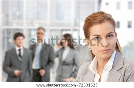 Closeup portrait of young attractive businesswoman, businesspeople in background of lobby.? - stock photo