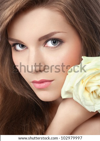 closeup portrait of young attractive girl with perfect skin and makeup, with a rose in her hand