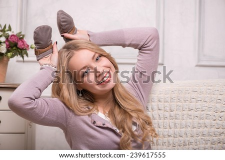 Closeup portrait of young attractive happy Caucasian woman sitting in armchair holding baby mittens and putting them by her head like rabbit ears, interior shot, baby expectation concept - stock photo
