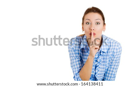 Closeup portrait of young, attractive, secret woman, showing silence sign, asking  to keep quiet, isolated on white background, copy space to the left. Human communication, facial expression, sign