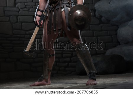 Closeup portrait of young attractive warrior gladiator with muscular body holding shield and axe, knees on dark background. Concept of masculine power, strength