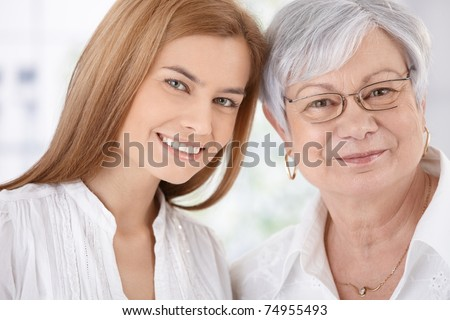 Closeup portrait of young attractive woman and senior mother, both smiling, looking at camera.?