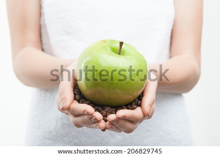 Closeup portrait of young attractive woman in white towel holding coffee beans and green apple, isolated on white - stock photo