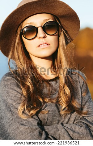 Closeup portrait of young beautiful blonde girl with fresh clean skin and blue eyes. Wearing hat and sunglasses. Outside - stock photo