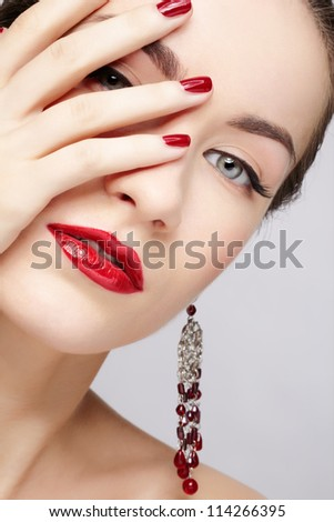 closeup portrait of young beautiful brunette woman in ear-rings closing half of her face with manicured hand - stock photo