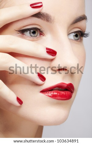 closeup portrait of young beautiful brunette woman in ear-rings touching her face with manicured hand - stock photo