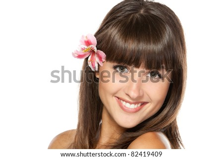 Closeup portrait of young beautiful female with flower over her ear, isolated on white background - stock photo