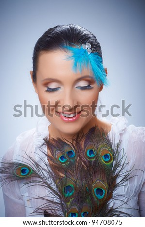 Closeup portrait of young beautiful girl with fantasy make-up with a peacock feather - stock photo