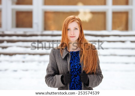 Closeup portrait of young beautiful redhead woman in blue dress and grey coat at winter outdoors - stock photo