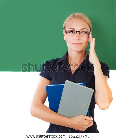 Closeup portrait of young beautiful teacher, smart student girl near green chalkboard in the university, educator in the school, education concept - stock photo