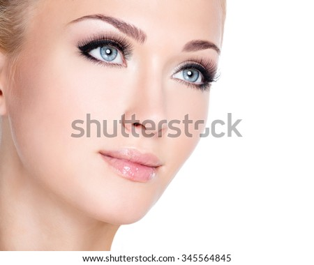 Closeup portrait of young beautiful white woman with long false eyelashes  over white background