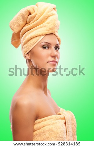 Closeup portrait of young beautiful woman after bath, on green background.