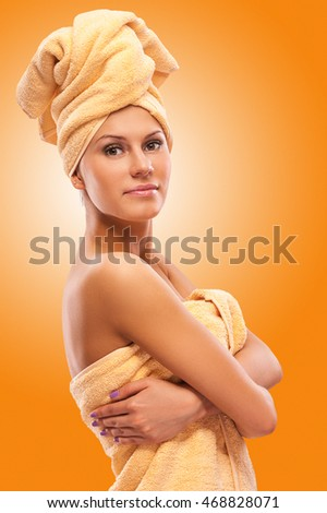 Closeup portrait of young beautiful woman after bath, on orange background.
