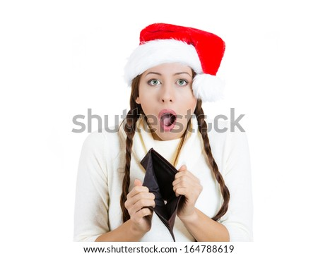 Closeup portrait of young beautiful woman in red santa claus hat, showing empty wallet, isolated on white background. Negative human emotion, facial expression. Holiday spending, shopping concept - stock photo