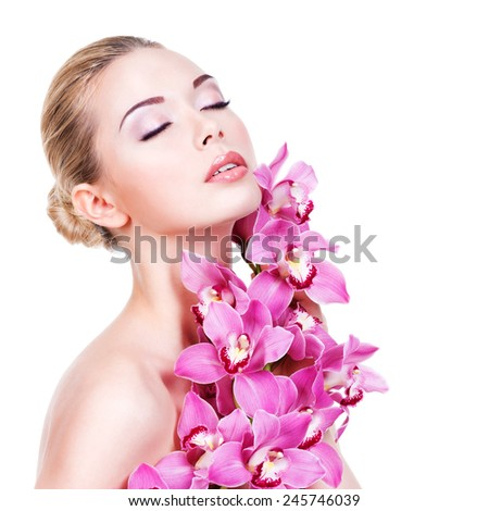 Closeup portrait of young beautiful woman with a healthy clean skin of the face. Pretty adult girl with flower near the face.  - isolated on white background - stock photo