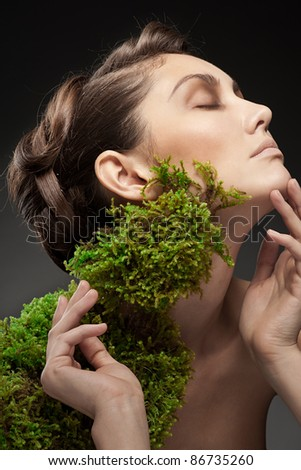 Closeup portrait of young beautiful woman with green moss growing on her neck - stock photo