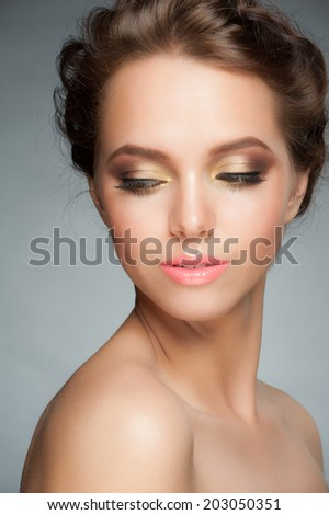 Closeup portrait of young beautiful woman with stylish makeup with golden eyeshadows - stock photo