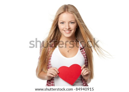 Closeup portrait of young blond female with lightly fluttering on the wind hair holding heart shape isolated on white background