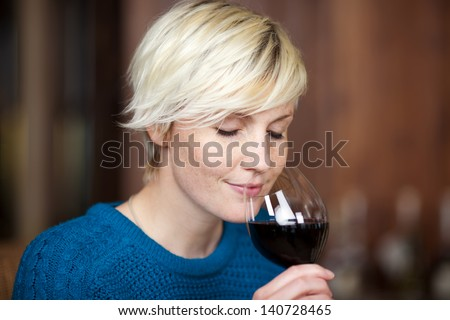 closeup portrait of young blond woman drinking red wine in restaurant - stock photo