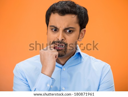 Closeup portrait of young business man thinking, daydreaming, trying hard to remember something, looking confused, biting nail, isolated orange background. Negative human emotion facial expression.  - stock photo