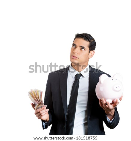 Closeup portrait of young business man with piggy bank in one hand and money in other, trying to decide on saving or spending. Negative emotion facial expression feelings, reaction. Financial dilemmas - stock photo