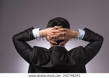 Closeup portrait of young businessman from the back. Sitting with opened arms on his armchair. Isolated over gray background - stock photo