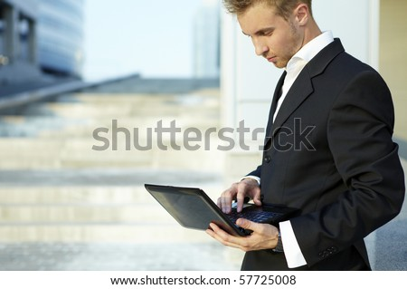Closeup portrait of young businessman using laptop on street - stock photo