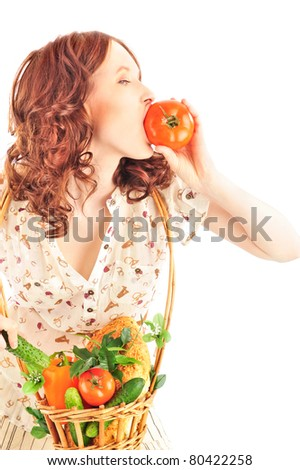 Closeup portrait of young caucasian woman with straw basket of fresh vegetables wearing trendy clothes isolated on white background. Eating her harvest - stock photo