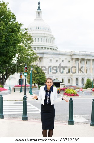 Closeup portrait of young clueless professional, federal employee, politician, businesswoman, executive, who can't answer the question, isolated on background Washington DC Capitol USA. Politics - stock photo
