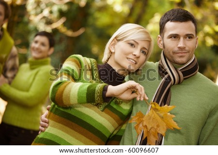 Closeup portrait of young couple embracing in autumn park, woman holding leaves.? - stock photo