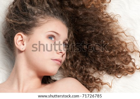 Closeup portrait of young emotional beautiful girl with perfect curly hair. Lying on white fur bed