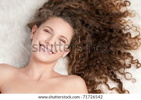 Closeup portrait of young emotional playful girl with perfect curly hair. Lying on white fur bed - stock photo