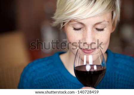 Closeup portrait of young female customer drinking red wine with eyes closed - stock photo