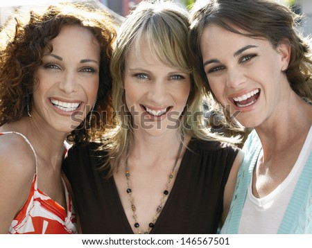 Closeup portrait of young female friends smiling outdoors - stock photo