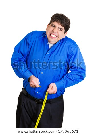 Closeup portrait of young frustrated, stressed man trying to pull measuring tape around paunch, but unable to because of size, isolated white background. Negative emotion facial expression feelings