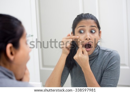 Closeup portrait of young frustrated woman surprised stunned to see zit on her face, gray turtleneck, isolated mirror reflection background. Facial  feelings, situation, reaction - stock photo
