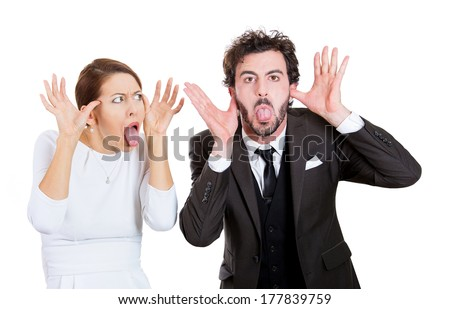 Closeup portrait of young funny looking couple man, woman sticking out tongues at you, camera gesture, thumbs hands on temple, isolated on white background. Human emotions, facial expression, attitude