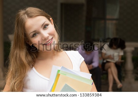 Closeup portrait of young girl with books outdoor. Students outside school holding books and smiling