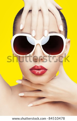 closeup portrait of young gorgeous caucasian woman wearing sunglasses, over yellow background - stock photo
