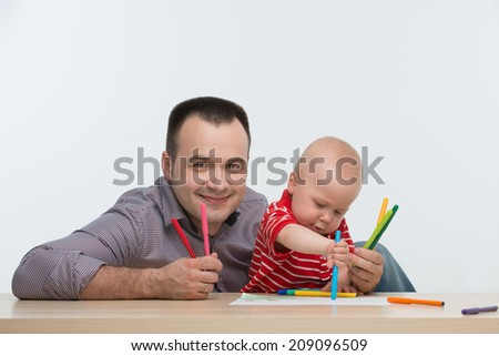 Closeup portrait of young handsome Caucasian father drawing with his cute toddler son, isolated on white - stock photo