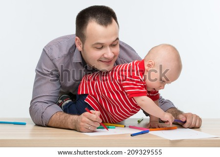 Closeup portrait of young handsome Caucasian father drawing with his cute toddler son sitting on the desk, isolated on white