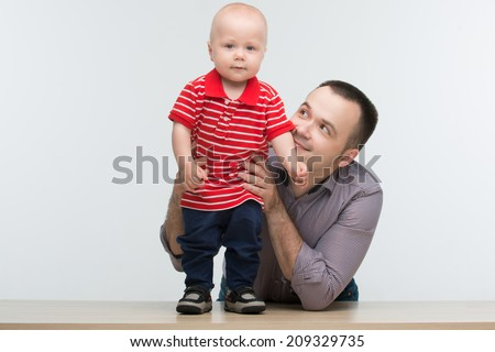 Closeup portrait of young handsome Caucasian father posing with his cute toddler son standing on the desk, isolated on white - stock photo