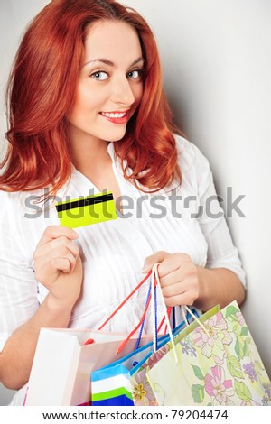 Closeup portrait of young handsome girl with red hair holding credit or debit card and three shopping bags. Standing near wall and smiling - stock photo