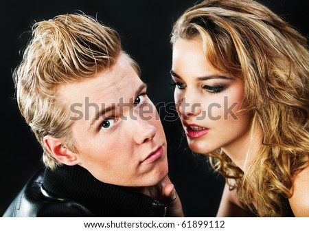 Closeup portrait of young handsome man and pretty woman in darkness - stock photo
