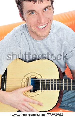 Closeup portrait of young handsome man playing his guitar sitting on sofa - stock photo